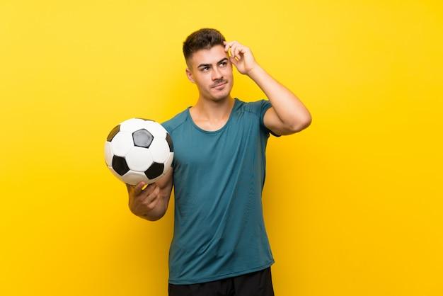 Hübscher junger fußballspielermann über der lokalisierten gelben wand, die zweifel und mit hat, verwirren gesichtsausdruck