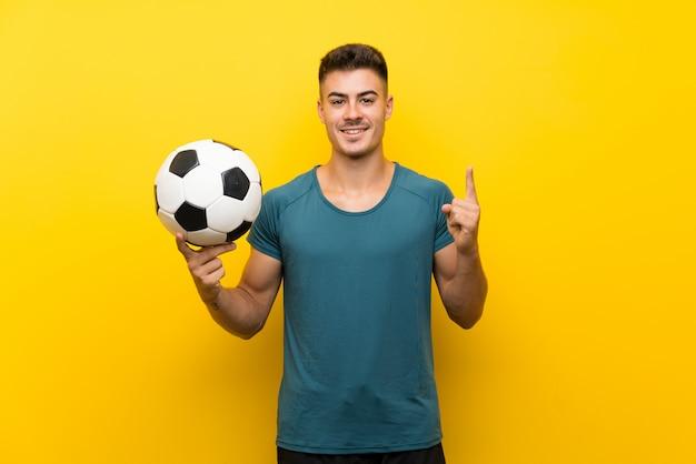 Hübscher junger fußballspielermann über lokalisierter gelber wand eine großartige idee oben zeigend