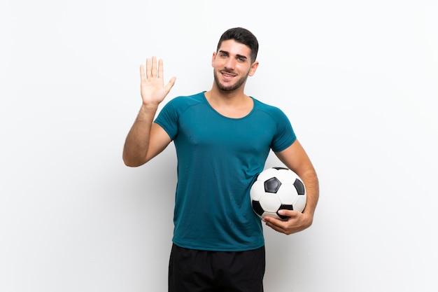 Hübscher junger fußballspielermann über weißer wand begrüßend mit der hand mit glücklichem ausdruck