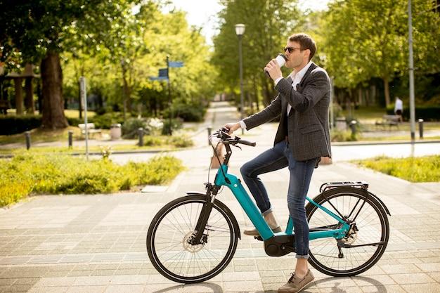 Hübscher junger geschäftsmann auf dem e-bike mit kaffeetasse zum mitnehmen