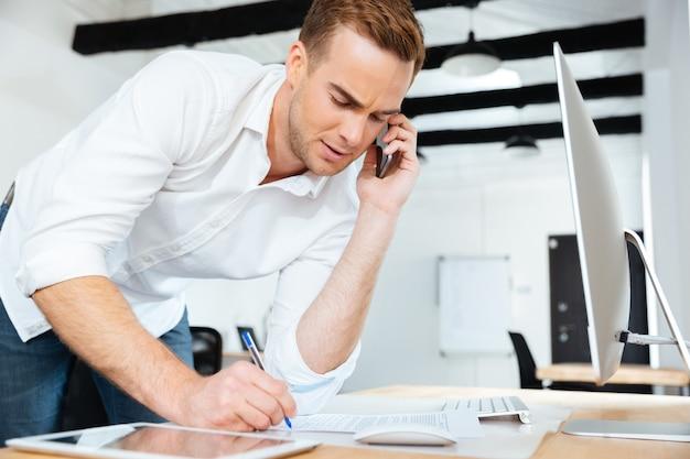 Hübscher junger geschäftsmann, der am handy spricht und im büro schreibt