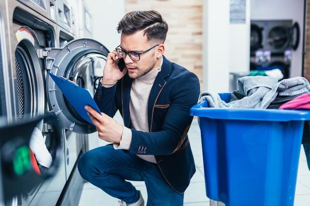 Hübscher junger geschäftsmann, der am handy spricht, während er seine wöchentliche wäsche in einem waschsalon tut.