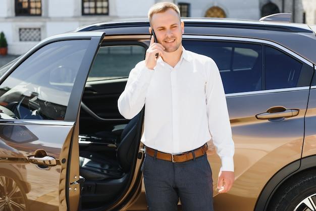 Hübscher junger geschäftsmann, der am telefon spricht, während er in der nähe seines autos draußen steht