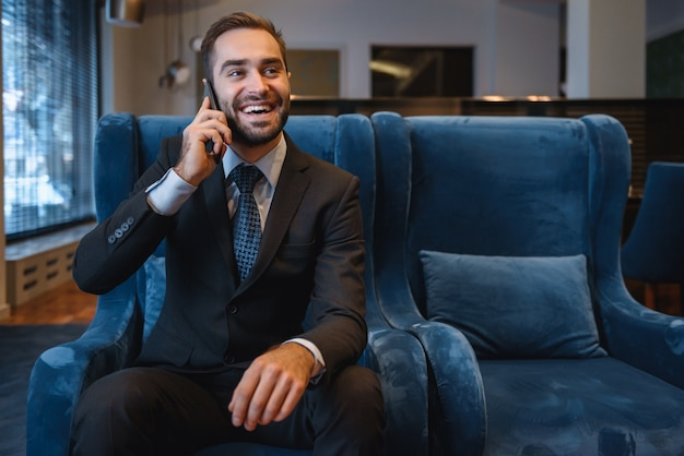 Hübscher junger geschäftsmann, der anzug sitzt, der an der hotellobby sitzt, das handy benutzt und erfolg feiert