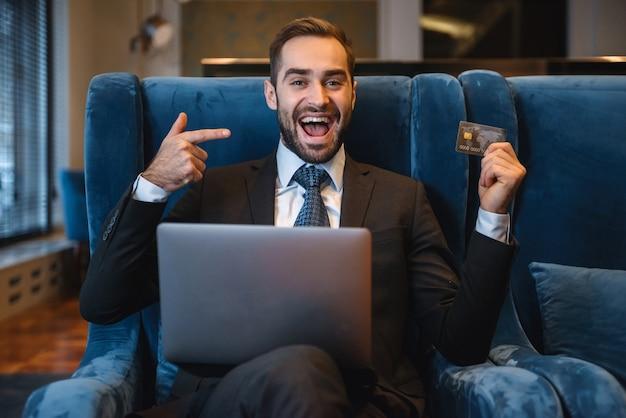 Hübscher junger geschäftsmann, der anzug sitzt, der an der hotellobby sitzt, laptop-computer benutzt, plastik-kreditkarte zeigend