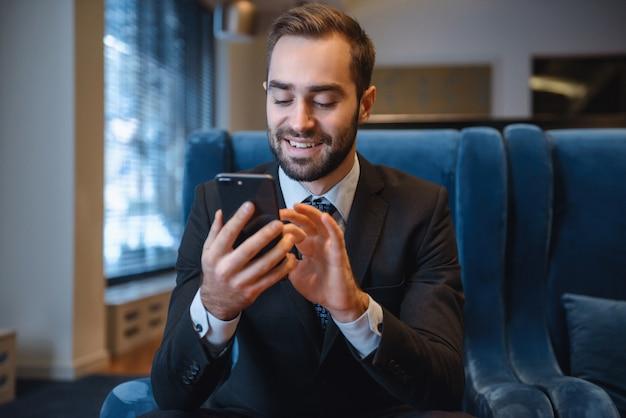 Hübscher junger geschäftsmann, der anzug sitzt, sitzt an der hotellobby, unter verwendung des mobiltelefons