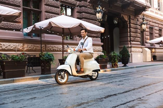 Hübscher junger geschäftsmann, der auf einem motorrad draußen auf einer stadtstraße reitet