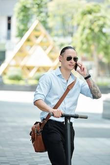 Hübscher junger geschäftsmann, der auf roller reitet und am telefon spricht