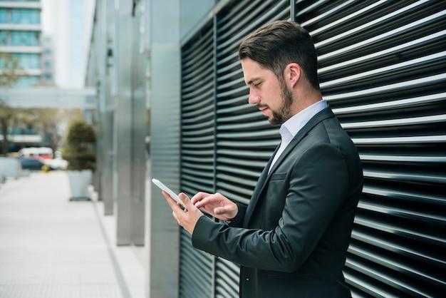 Hübscher junger geschäftsmann, der außerhalb des büros unter verwendung des intelligenten telefons steht