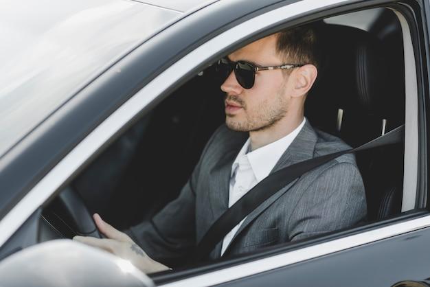 Hübscher junger geschäftsmann, der auto fährt