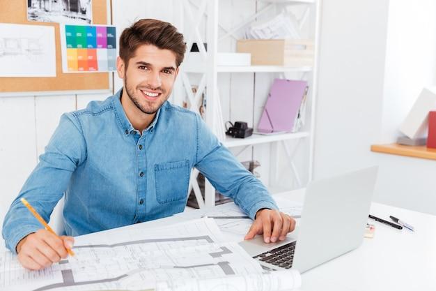 Hübscher junger geschäftsmann, der bleistift hält und mit dokumenten im büro arbeitet