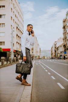 Hübscher junger geschäftsmann, der ein mobiltelefon benutzt, während er eine straße betritt