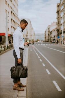 Hübscher junger geschäftsmann, der ein mobiltelefon verwendet, während auf ein taxi wartet, das ein taxi auf einer straße wartet