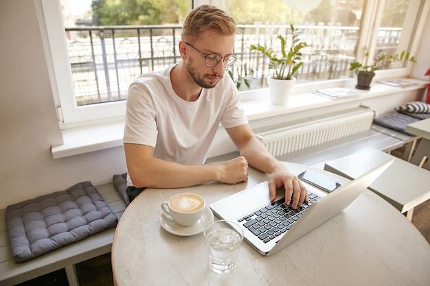 Hübscher junger geschäftsmann, der in einem café mit tasse kaffee und laptop sitzt, brille und freizeitkleidung trägt und konzentriert und nachdenklich aussieht