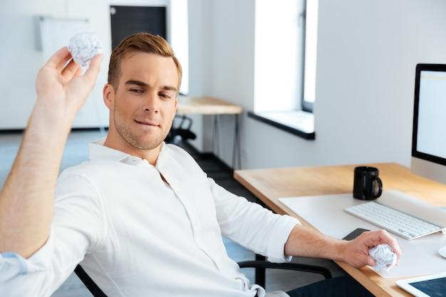 Hübscher junger geschäftsmann, der papier im büro zerknittert und wirft