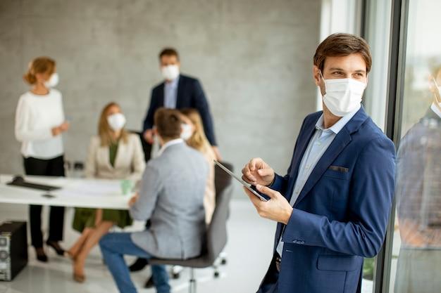 Hübscher junger geschäftsmann, der schützende gesichtsmaske trägt, während digitales tablett im büroraum hält