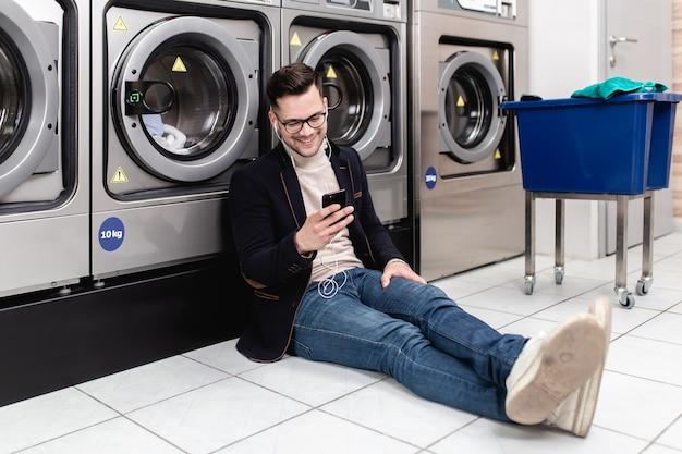 Hübscher junger geschäftsmann, der seine wöchentliche wäsche in einem waschsalon tut.