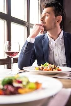 Hübscher junger geschäftsmann, der während eines business-lunchs isst.