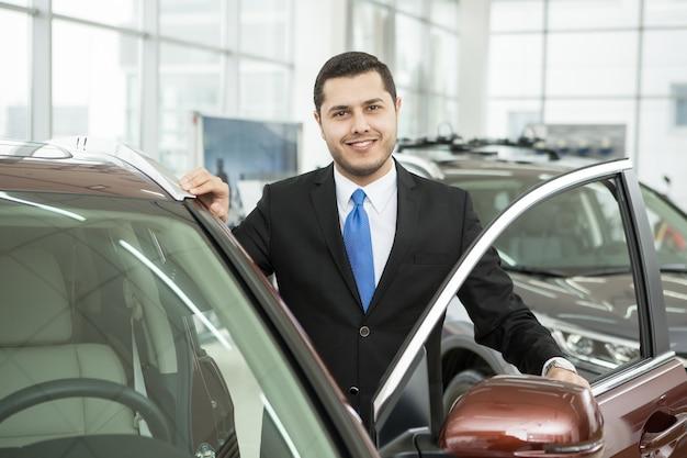 Hübscher junger geschäftsmann, der zur kamera lächelt, die nahe einem neuen auto steht