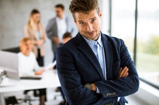 Hübscher junger geschäftsmann, der zuversichtlich im büro vor seinem team steht