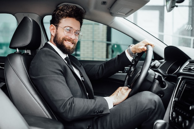 Hübscher junger geschäftsmann im vollen anzug, der beim fahren eines neuen autos lächelt