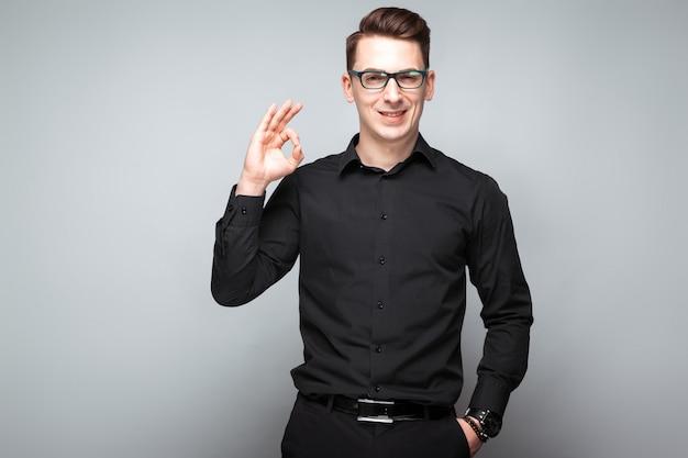 Hübscher junger geschäftsmann in der kostspieligen uhr, in den schwarzen gläsern und im schwarzen hemd