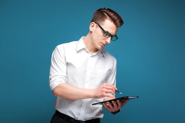 Hübscher junger geschäftsmann in der kostspieligen uhr, in den schwarzen gläsern und in der weißen hemdgrifftablette und -stift