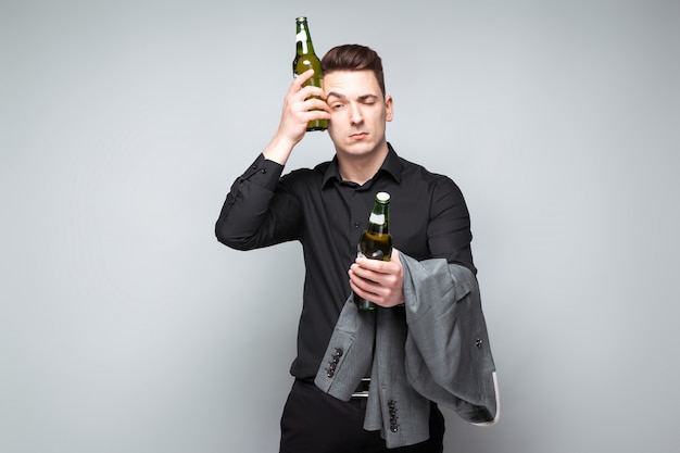 Hübscher junger geschäftsmann in der kostspieligen uhr und im schwarzen hemd halten graue jacke und bier