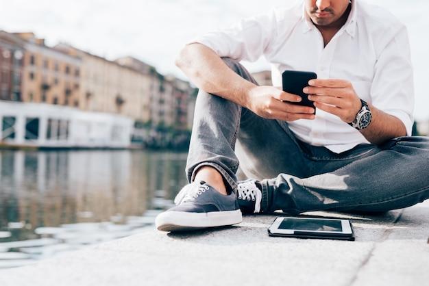 Hübscher junger geschäftsmann in einem weißen hemd gesetzt durch das wasser unter verwendung des smartphone