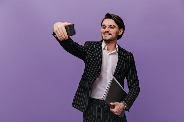 Hübscher junger geschäftsmann mit brünetten haaren, brille, weißem hemd und gestreiftem anzug, lächelnd, selfie machen und ordner in einer hand halten