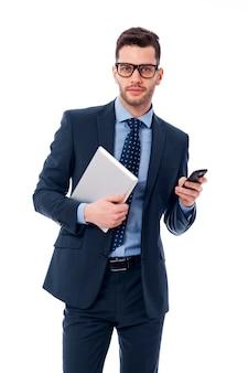 Hübscher junger geschäftsmann mit einem digitalen tablett und einem mobiltelefon