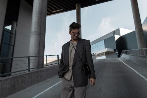 Hübscher junger geschäftsmann mit frisur in einem modischen anzug mit sonnenbrille geht in die stadt. männlicher stil, schönheit und erfolg