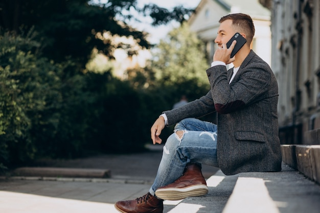 Hübscher junger geschäftsmann mit telefon außerhalb der straße