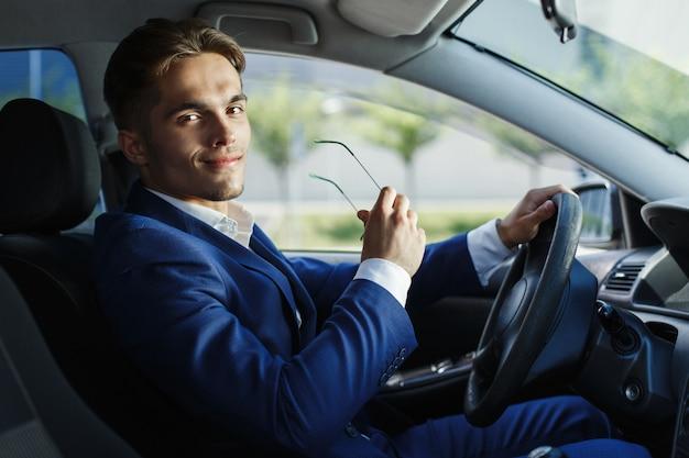 Hübscher junger geschäftsmann sitzt am lenkrad innerhalb des autos