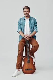 Hübscher junger gitarrist lächelt und schaut in die kamera, während er vor grauem hintergrund sitzt