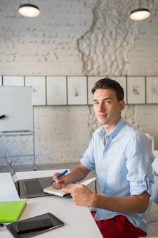 Hübscher junger gutaussehender mann, der denkt, notizen in notizbuch schreibt