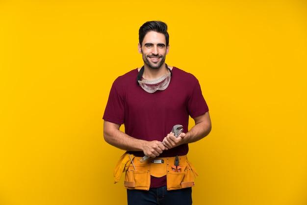 Hübscher junger handwerker über lokalisiertem gelbem hintergrund