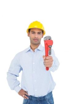 Hübscher junger heimwerker, der einen rohrschlüssel hält