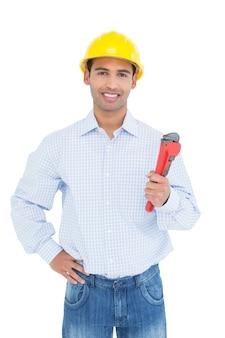 Hübscher junger heimwerker, der rohrschlüssel hält