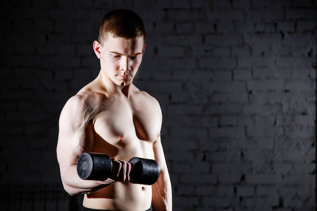 Hübscher junger hemdloser mann mit dem muskulösen sexy körper, der übungen unter verwendung des dummkopfs gegen eine backsteinmauer tut.