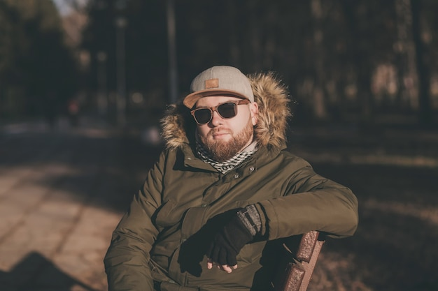 Hübscher junger hipster-mann in der sonnenbrille, die draußen auf einer bank sitzt
