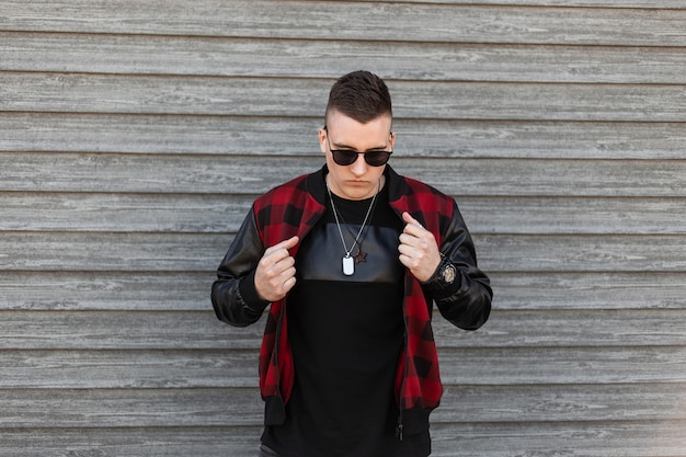 Hübscher junger hipster-mann in einer stilvollen karierten jacke in einem trendigen schwarzen t-shirt mit schwarzer sonnenbrille posiert in der nähe einer hölzernen vintage-wand