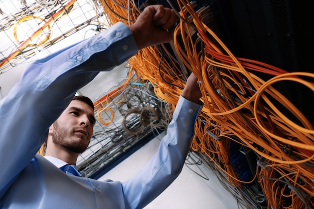 Hübscher junger ingenieur, der kabel im serverraum anschließt