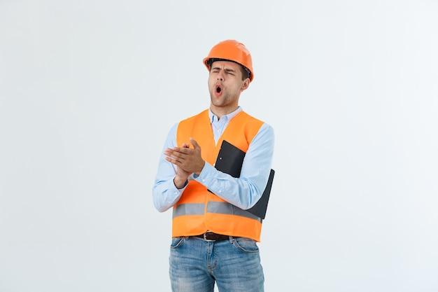 Hübscher junger ingenieur über grauem schutzhelm mit schockiertem überraschungsgesicht.