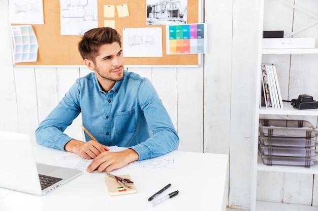 Hübscher junger intelligenter geschäftsmann, der mit dokumenten und computer im büro arbeitet