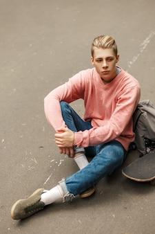 Hübscher junger jugendmann in einem rosa pullover mit einem skateboard und einem rucksack sitzt auf dem asphalt