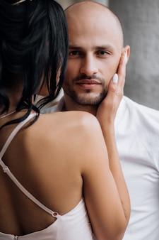 Hübscher junger kahlköpfiger mann umarmt mit jungem brunette der leidenschaft im rosa abendkleid