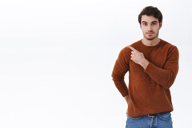 Hübscher junger kaukasischer mann, der mit dem finger oben links zeigt