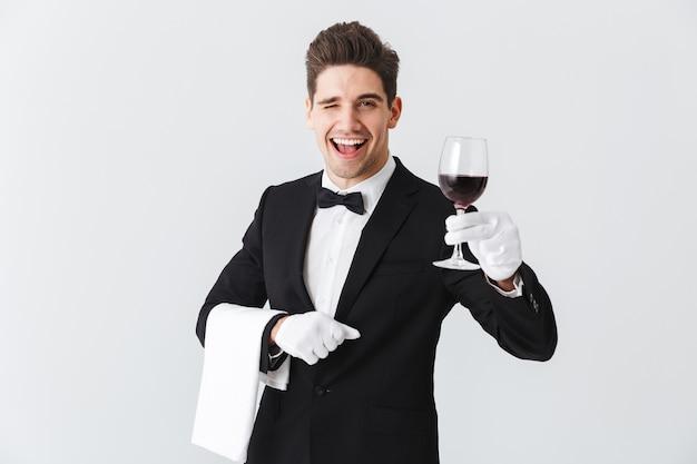 Hübscher junger kellner, der smoking hält glas des rotweins lokalisiert über graue wand