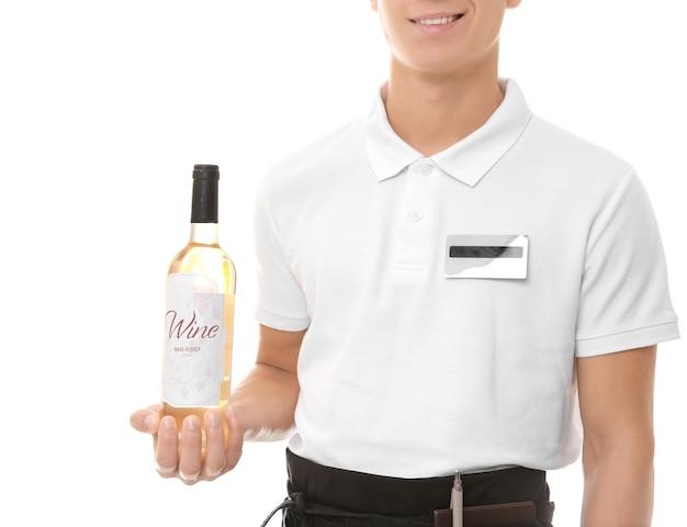 Hübscher junger kellner mit flasche wein auf weißer wand